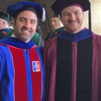 Eric Vallender, wearing his UChicago gown, with a colleague at a University of Mississippi Commencement ceremony.