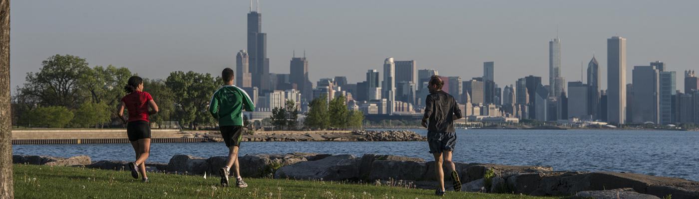 UChicago students run near the lake with a view of the skyline.