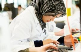 A woman wearing a head scarf in a lab.
